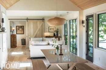 Living area featuring barn doors, an off-white sofa and a picnic-bench dining room table