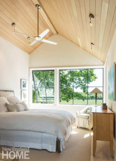 Master bedroom with a bed covered in white bedding. There's a ceiling fan hanging from the pitched roof over the bed. Windows look out on the green yard.