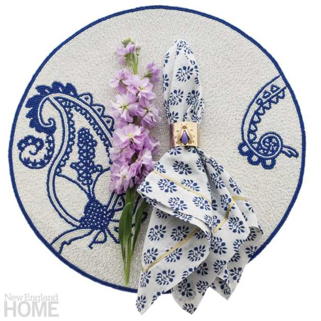 A round blue and white placemat with a blue and white napkin secured in a gold napkin ring resting on top
