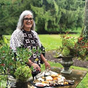 The artist who has long gray hair and black rimmed glasses. She's wearing a flowered smock.