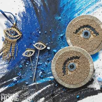 Two coasters, two cocktail picks and an ornament in gold with blue evil eyes created in beads