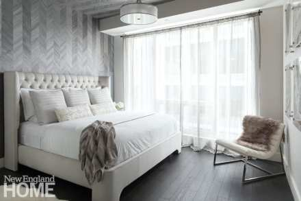 Master bedroom in white and light gray. There's a bed in white coverings, and a large window with white shears