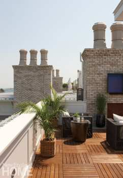 Roof deck with brick chimneys, teak floor and palm trees in baskets