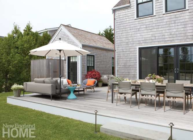 The generous deck wraps around the living room, increasing the home's livable space. Interior designer Audrey Sterk elevates the outdoor area's allure—as she has the whole house—with comfortable pieces that correlate with easy living and relaxation. The adjacent guest house/studio mimics the home's design and provides bonus overnight accommodations.