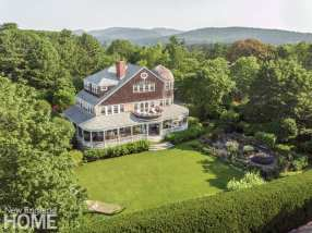 An aerial view of the home's exterior with wrap-around porch, lush green lawn and forest of trees. You can see rolling green hills in the background.