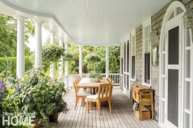 On the wraparound porch, you have a rectangular table made of light-colored wood and adorned with a plant. There's also a side table under a window.