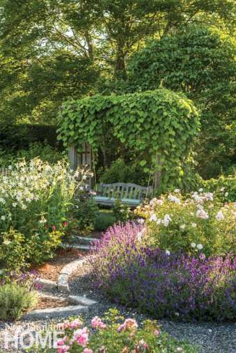 A lush garden filled with purple, pink, white and red flowers. There's a swing shrouded in green ivy.