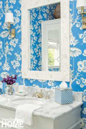 Close-up shot of a vanity with a mirror above it against bright blue wallpaper adorned with white flowers