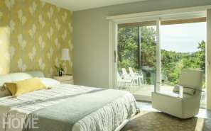 A top-floor guest bedroom has a wide balcony for enjoying the view.