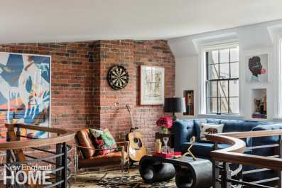 Julian Edelman's lounge with a brick wall adorned with a dart board. There's an acoustic guitar leaning up against the wall.