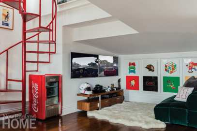Julian Edelman's Game room with dark wood floors, a red spiral staircase and a small Coke machine.