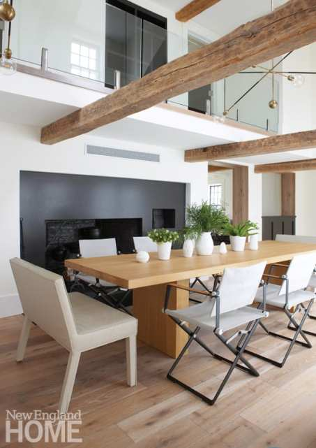 Dining rooms with rectangular table and a huge fireplace behind it. Above the table are exposed beams and then a glimpse into the second floor