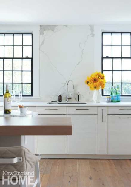 An up-close view of the white kitchen cabinets and marble backsplash