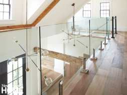 Wood floors in the loft hallway and glass walls looking down on wood beams