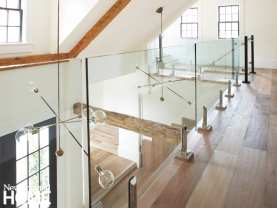 Wood floors in the loft hallway and glass walls looking down on wood beams