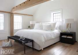 Bedroom with wood floors, white bedding, white walls and wood beams