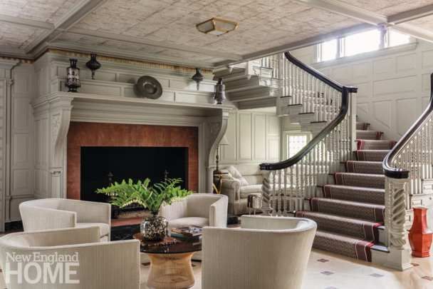 Entryway with low ceiling and massive fireplace. There's a carpeted stairway off to the right.