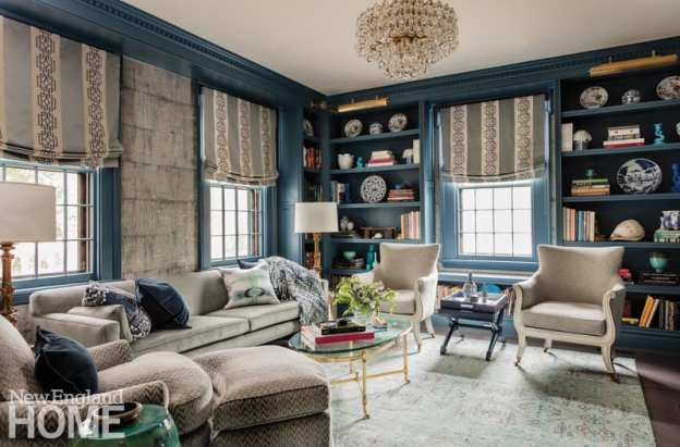 Library with blue walls and bookshelves. There are roman shades on the windows. The couch and chairs are various shades of gray and beige.