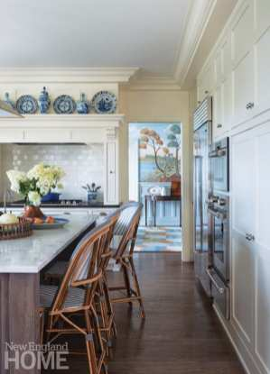 Kitchen with bistro chairs at the counter and a view of the mural in the formal dining room
