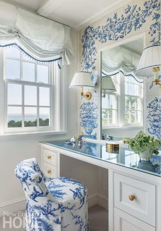 a white vanity with a blue and white upholstered chair