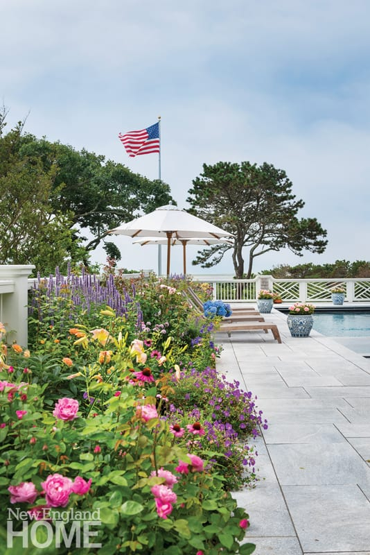 backyard garden in bloom with a deck, chaise lounges and a pool