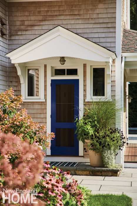 blue front door of shingle-style home