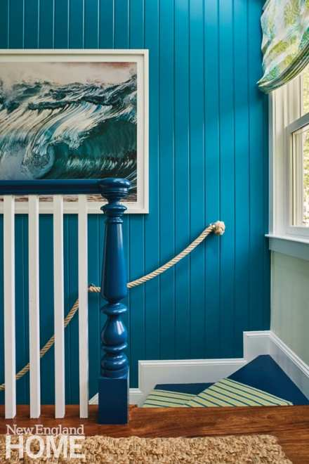 blue shiplap wall behind the blue railing of a staircase
