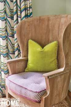 detail of a wood chair with a green accent pillow