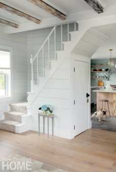 The ground-floor walls and the home's original staircase now wear horizontal shiplap for a traditional Cape Cod cottage feel.