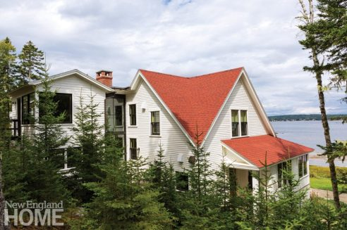 Cream colored home with red roof and water in the background