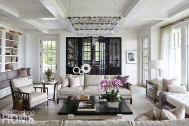 The living room is glamorous and comfortable in equal measure; the black doors open to the roomy bar.
