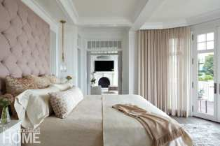 The master bedroom's tufted headboard and diaphanous drapes add even more elegance to a glam space.