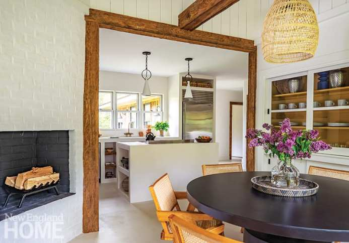Kitchen and dining area with white walls and rustic beams