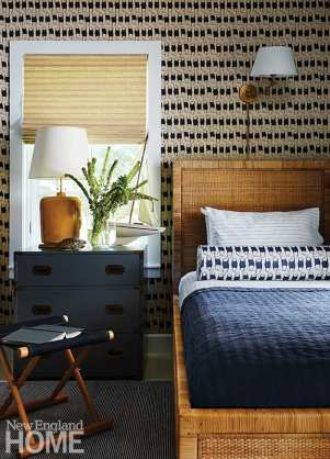Texture rules in a playful guest bedroom, where hand-blocked fabric by Design No. Five covers walls and a pillow. A vintage campaign chest was painted inky grey, while the model sailboat comes from Thoreauly Antiques in Concord.