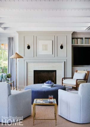 To draw the eye upward in the long, open-plan living area, interior designer Lisa Tharp added beams and rafters to ceilings, hung drapes as high as possible, and replaced the existing fireplace surround with floor-to-ceiling paneling.