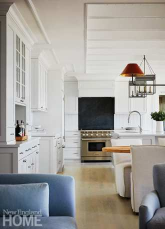 In the kitchen, astragal molding was carried from the upper cabinets onto the ceiling, drawing the focal point up. The same style molding was used to frame ceiling beams. The Urban Electric Co. lanterns and a pendant light hang above the island and table.