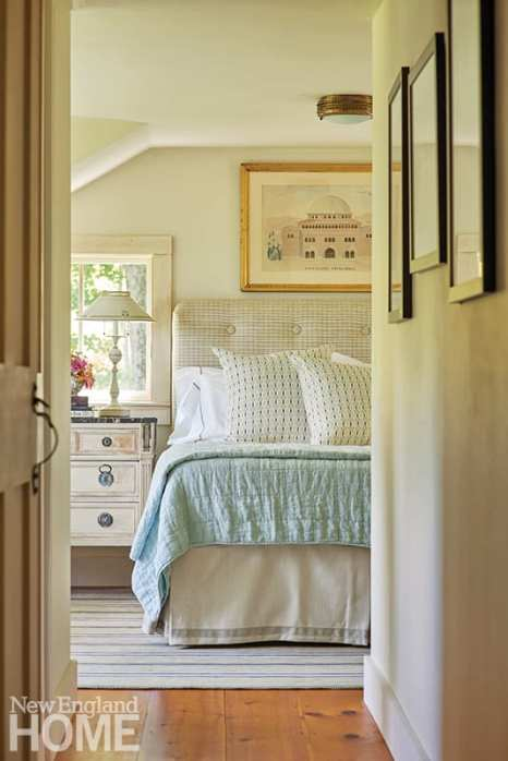 Master bedroom with white linens and antique prints