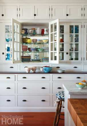 "Skok loves the double-sided glass cabinets filled with vintage treasures: ""When the cabinets are lit during a dinner party, everything twinkles,"" she says."