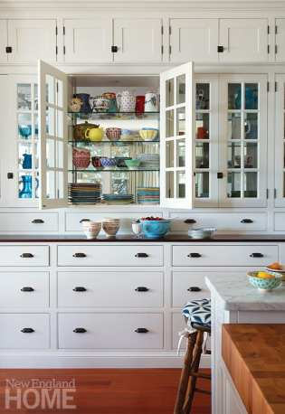 """Skok loves the double-sided glass cabinets filled with vintage treasures: """"When the cabinets are lit during a dinner party, everything twinkles,"""" she says."""