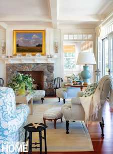 The living room's stone fireplace was inspired by the one in the original house; that's Skok's Nichola fabric on the French footstool.