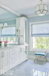 Bathroom with white cabinetry and light blue walls.