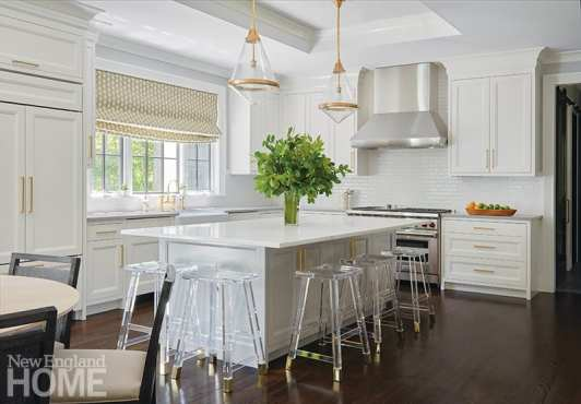 White kitchen with brass and glass pendants and lucite stools.