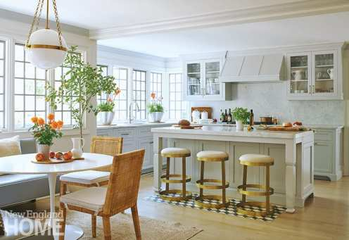 Neutral kitchen with brass bar stools and rattan chairs