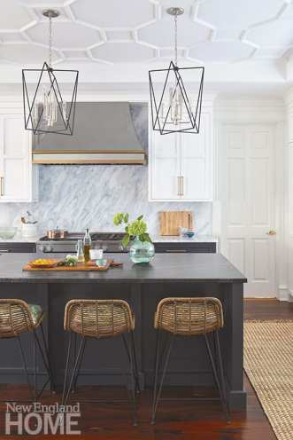 The new kitchen island boasts seating for five at Palecek bar stools perched beneath pendants from Hudson Valley Lighting.