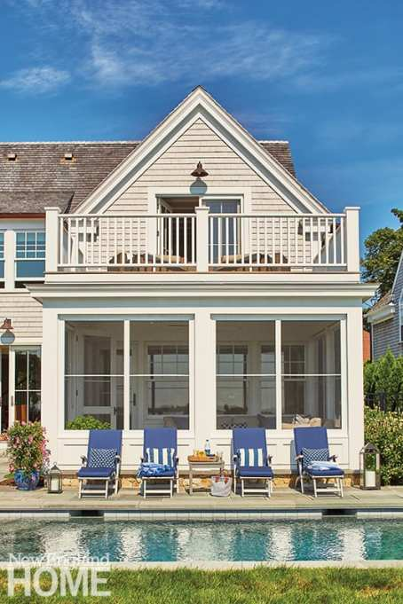 Varied rooflines and dormers help scale down what is essentially a tall, skinny house; the three-season porch and master balcony are stacked above an inground pool with water views.