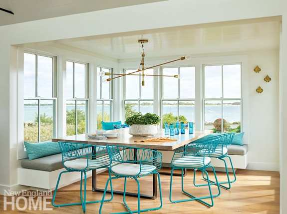 Crestin designed the custom table, built by Grace Woodworking, to seat a crowd; outdoor chairs from West Elm keep the vibe casual and give the dining nook a hit of color.