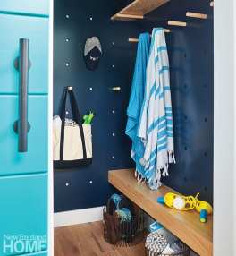 A giant pegboard, fabricated by Premier Builders, allows flexibility in the small mudroom as the homeowners can move the pegs to accommodate life vests, towels, and jackets.