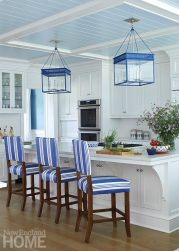 Multiple dining options include an island with generous storage and pendant lighting. A milky-blue coffered beadboard ceiling lends warmth to a breakfast nook, while dotted chair cushions play o