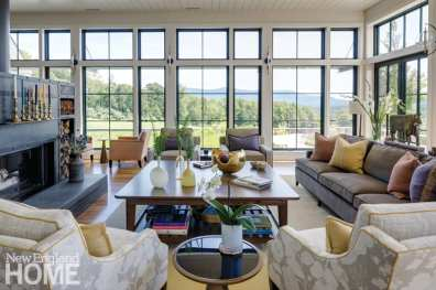 The gray metal of the fireplace contrasts with the pristine white subway tiles of the kitchen wall. The seating area has unobstructed views across a spacious meadow toward the hills.