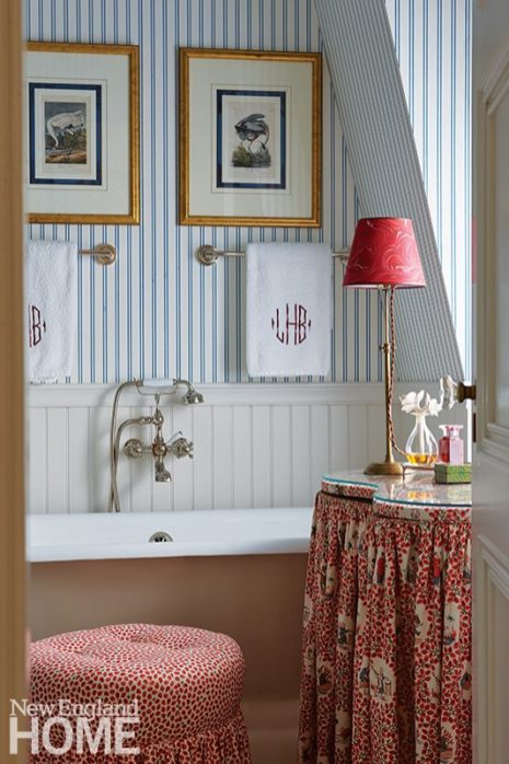 A blue-and-white-striped wallpaper by Hinson envelopes the main bathroom.